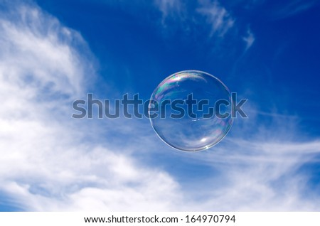 Soap bubble fly in mid-air in sunny day against blue sky with white clouds. concept photo of freedom and happiness - stock photo