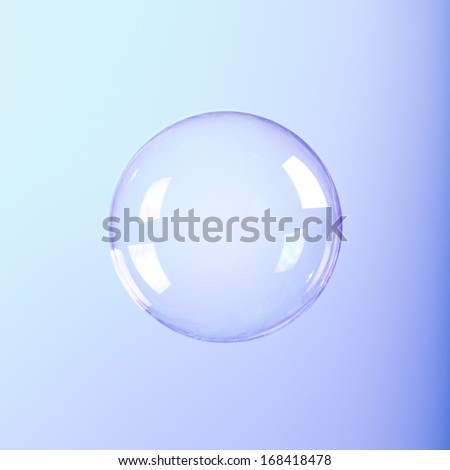 Soap Bubble isolated on blue gradient background. - stock photo