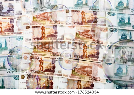 SOAP bubbles against a backdrop of banknotes in five and one thousand rubles