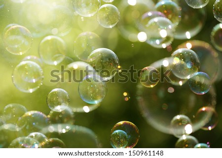 Soap bubbles floating in the air as the Summer sun sets - stock photo