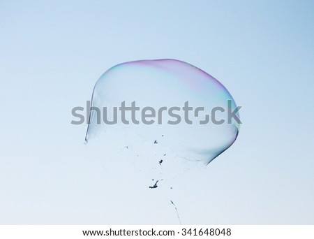 Soap bubbles popping blue sky illuminated by the sun texture background with copy space - stock photo