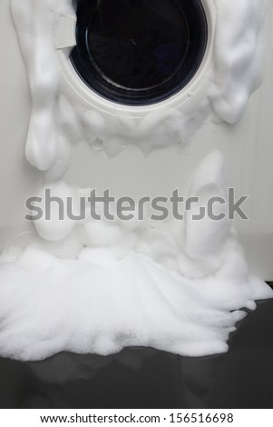 soap coming out from broken washing machine - stock photo