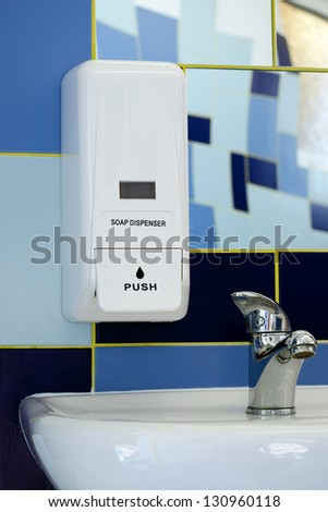 Soap dispenser above the sink or basin in blue tile bathroom. - stock photo