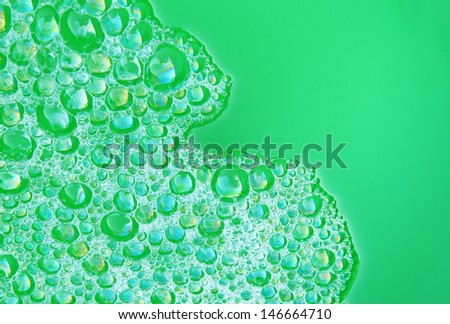Soap foam and bubbles in green container