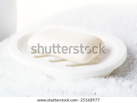Soap lays on a support on a white towel