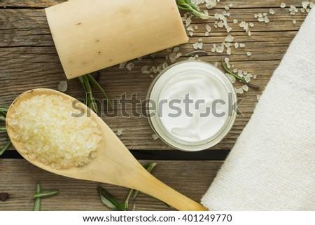 Soap, sea salt, face cream and towel top view selective focus - stock photo