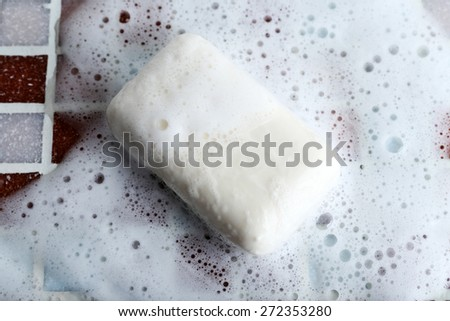 Soap with bubble on mosaic tiles background - stock photo