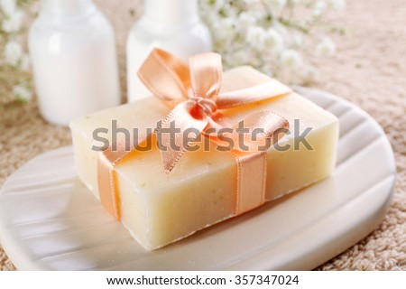 Soap with ribbon on a dish over towel background, close up - stock photo