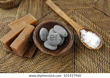 Soaps and stones in bowl with salt in wooden spoon on straw mat