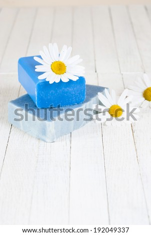 soaps with herbal flowers on white wood table