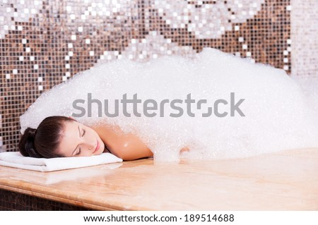 Soapy pleasure. Beautiful young woman relaxing in Turkish bath with foam  - stock photo