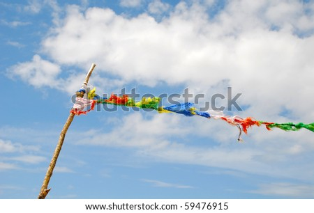 Soaring flag against the blue sky. The flag is made of fabric slices. - stock photo