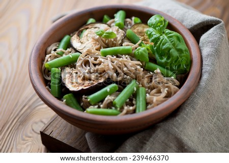 Soba noodles with aubergine, beans and sesame, close-up