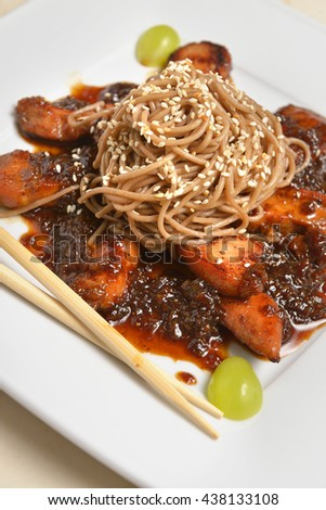 Soba noodles with chicken breast , decorated with sesame seeds and grapes