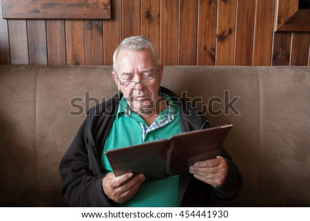 Sober senior man smiling and reading a restaurant menu ready to order food - stock photo