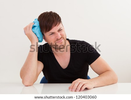 Sober young handsome guy got headache and applying ice bag - stock photo