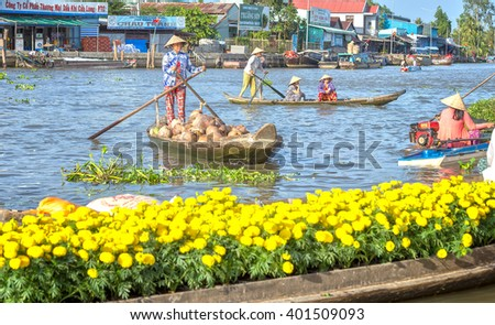 Soc Trang, Vietnam - February 2nd, 2016: Farmers selling coconut boating on river busiest air boats back forth, front bright yellow daisies boatload real river scene beauty in Soc Trang, Vietnam