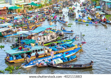 Soc Trang, Vietnam - February 3rd, 2016: Bustling produce market in morning on river with hundreds boats gathered fruit, flowers, vegetables traded on confluence river culture water Soc Trang, Vietnam