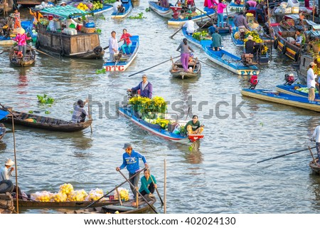 Soc Trang, Vietnam - February 3rd, 2016: Couple sold daisies boatman, watermelon, many boats around the busiest crossing in morning floating market on river in the countryside in Soc Trang, Vietnam