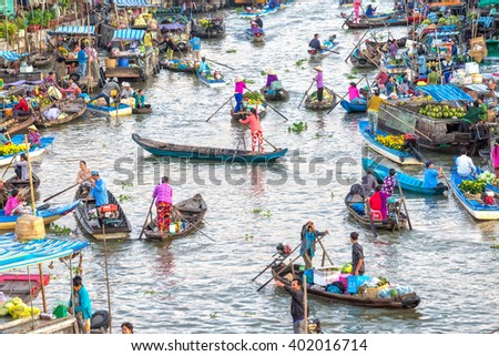 Soc Trang, Vietnam - February 3rd, 2016: Customers go market on river for women with colorful rowing boats clothes shopping agricultural products in morning floating market Soc Trang, Vietnam