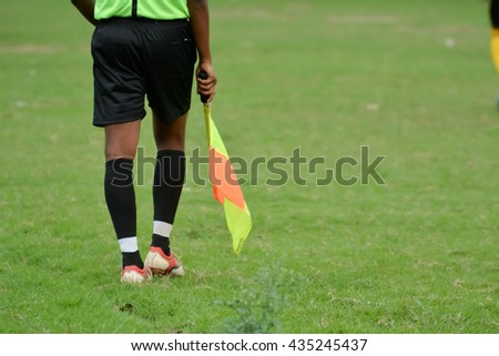 Soccer assistant referee is running with flag.