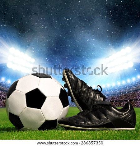 Soccer ball and cleats in grass, soccer stadium with the dright lights - stock photo