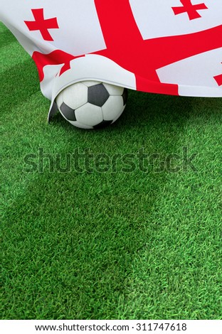 Soccer ball and national flag of Georgia lies on the green grass