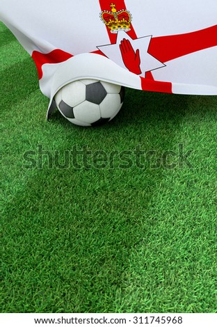 Soccer ball and national flag of Northern Ireland lies on the green grass