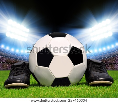 Soccer ball and shoes in grass, soccer stadium with the dright lights - stock photo