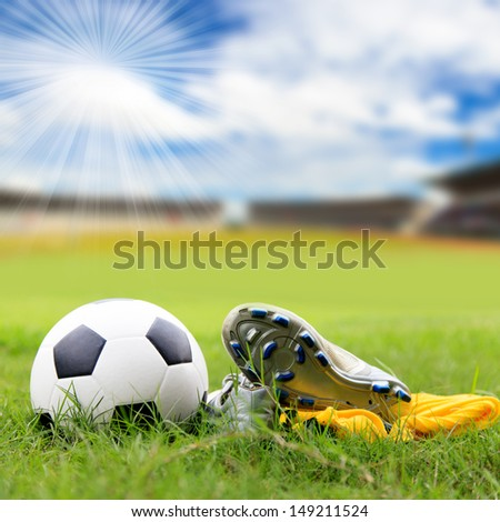 Soccer ball and soccer shoes on the field - stock photo