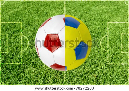 Soccer ball colored by flag of Poland and Ukraine at green grass