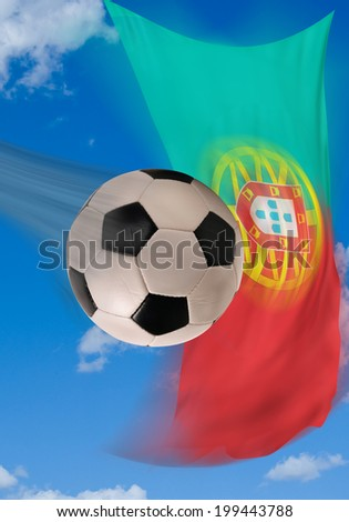 Soccer ball flying fast with Portugal flag in background. - stock photo