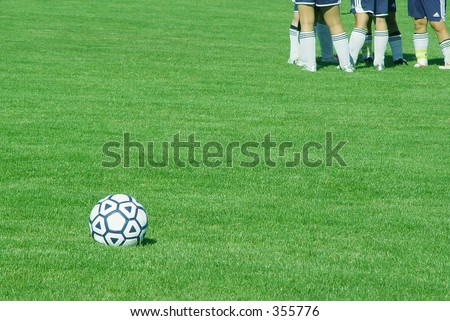 soccer ball in foreground, group of players in background - stock photo