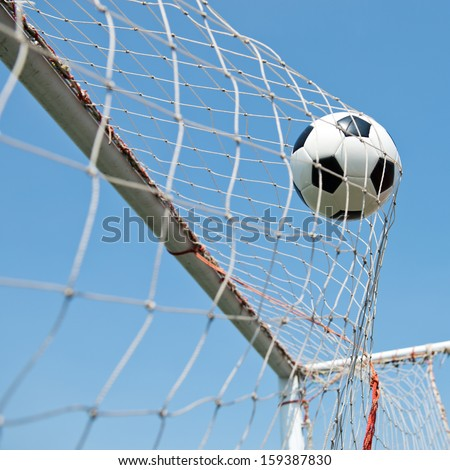 soccer ball in goal. isolated on blue sky background  - stock photo
