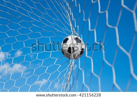 soccer ball in goal net with blue sky - stock photo
