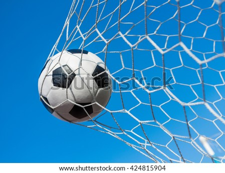 soccer ball in goal net with blue sky