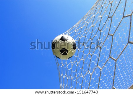 soccer ball in goal with blue sky - stock photo