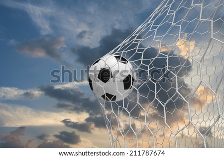 soccer ball in goal with sky - stock photo