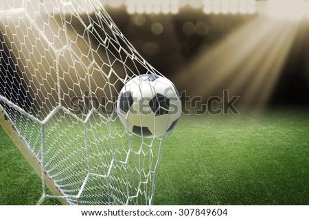 soccer ball in goal with spotlight - stock photo