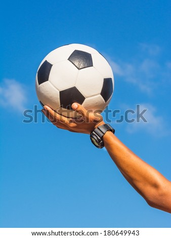 Soccer ball in hand and blue sky