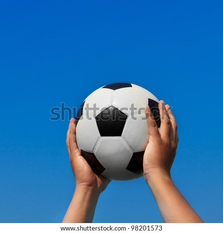 Soccer ball in hand on blue sky background.