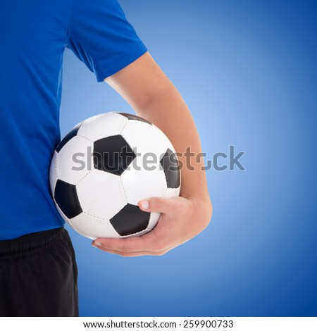 soccer ball in player's hand over blue background