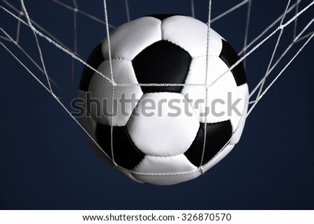 Soccer ball in the net on blue background - stock photo