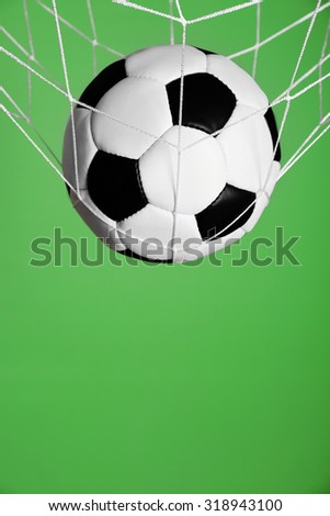 Soccer ball in the net on green background - stock photo