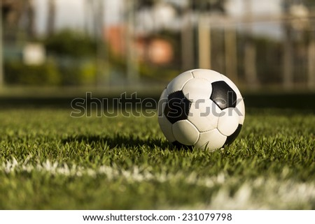 Soccer ball on a grass field, under the sunset. - stock photo