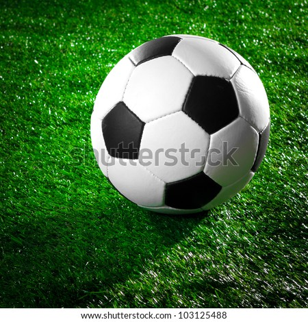 Soccer ball on a green grass lawn - stock photo