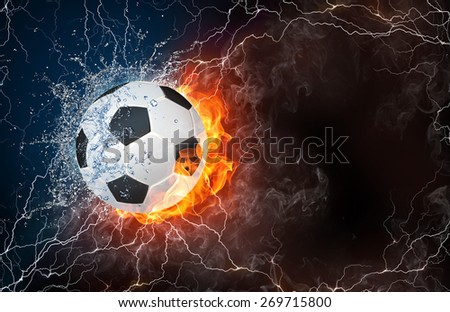 Soccer ball on fire and water with lightening around on black background. Horizontal layout with text space. - stock photo