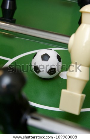 Soccer ball on foosball table - stock photo