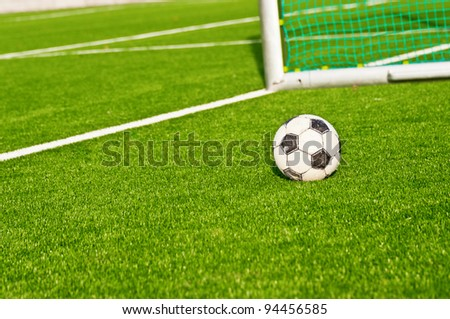 Soccer ball on  football field with football goals background