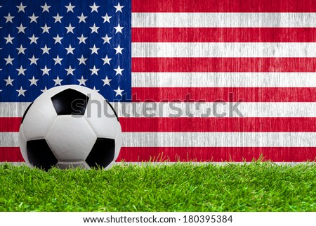 Soccer ball on grass with US flag background close up - stock photo